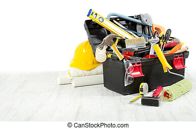 Tools in toolbox over wooden floor against empty wall. Copy space.