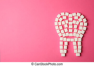 Tooth made of sugar cubes on pink background, top view