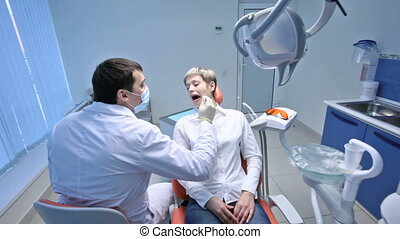 Toothache - Crane shot of dentist examining oral cavity of a...