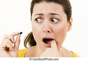 Toothache - Scared woman with toothache holding a pill