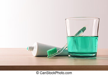 Toothbrush toothpaste and mouthwash on the wooden table...