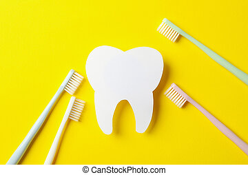 Toothbrushes and tooth on yellow background, top view