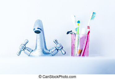 Toothbrushes on basin near water tap - Plastic glass with ...