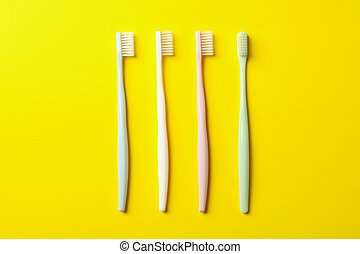 Toothbrushes on yellow background, top view. Dental care