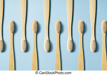 Toothbrushes regularly arranged on a blue background