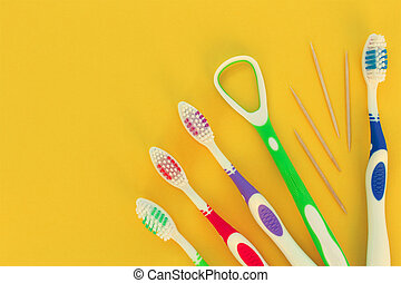 Toothbrushes, toothpick, tongue scraper on a yellow background. Top view.