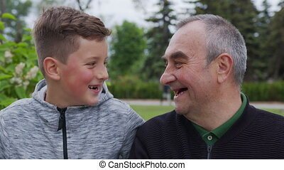 Toothless grandfather and grandson are laughing. Closeup. - ...