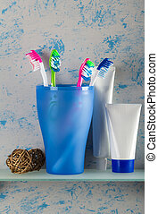 Toothpaste and toothbrushes on shelf - Toothpaste and...
