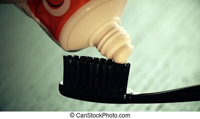 Toothpaste being put onto the black toothbrush - Toothpaste...