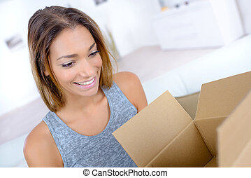 toothy smile woman opening parcel at home
