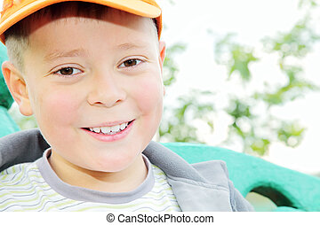 Toothy smiling boy outdoors