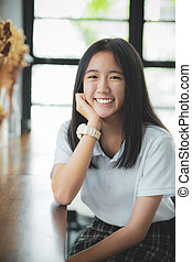 toothy smiling face of asian teenager looking with eye contact
