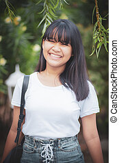 toothy smiling face of asian teenager standing outdoor happiness emotion
