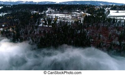 Top 4k aerial drone panorama flyover in blue dense cloud sky over stunning snow mountain forest evening sunset landscape