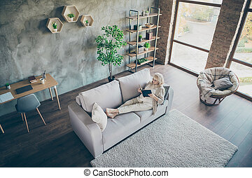 Top above high angle view of her she nice lovely focused gray-haired blond middle aged grandma reading love story at open space industrial brick loft modern style interior house apartment