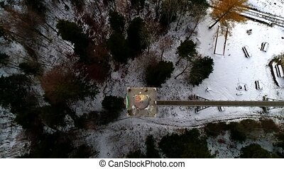 Top aerial drone 4k time lapse shot on flying up above in sky over dark pine tree winter forest covered in snow