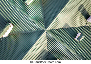 Top aerial view of building green shingle tiled roof construction. Abstract background, geometrical pattern.