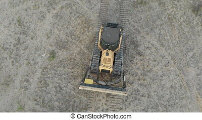 Top Aerial view on Tracked Bulldozer Rides on the Sandy Road at a Construction Site. Aerial tracking shot of a yellow excavator driving over rough terrain. The camera follows the bulldozer. Drone view