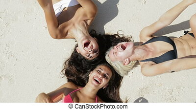 Top Angle View Of Three Girls Lying On Beach Laughing, Enjoy...