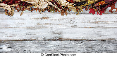 Top border of Autumn decorations on white rustic wooden boards for the holiday season