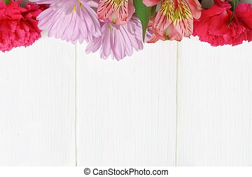 Top border of pink flowers against white wood