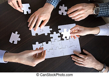 Top close up view of hands engaged in assembling puzzle