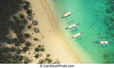 Top down aerial of sand beach with boats at ocean coast. ...