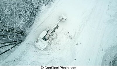 Top down aerial view of a crawler excavator in the snow