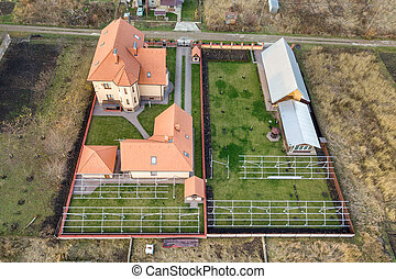 Top down aerial view of a private house with red tiled roof and frame structure prepared for installation of solar panels.