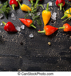 top down of yellow, orange and red hot chili peppers, sea salt, greenery, black pepper on cracks black background, close up