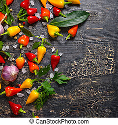 top down of yellow, red hot chili peppers, sea salt, greenery, black peppers and garlic on cracks black background, close up
