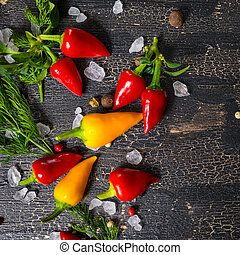 top down of yellow, red hot chili peppers, sea salt, greenery, jamaican peppers on cracks black background, close up