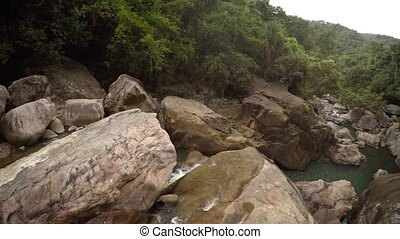 Top-down perspective of water tumbling over a natural waterfall in a Nha Trang Vietnam wilderness area, with sound. UltraHD video