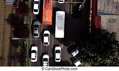 Aerial view of the vehicular intersection, traffic at peak hour with cars on the road, fly under trees.