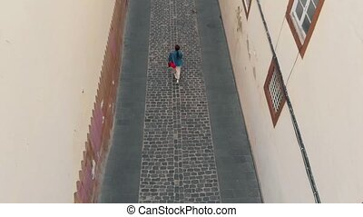 Top down view. A young woman walks along a narrow street of the old town in the capital of the island of Gran Canaria, a bird's-eye view.