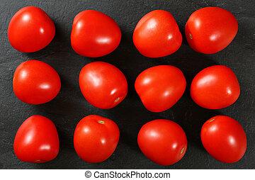 Top down view, dozen of mini tomatoes arranged on black stone desk