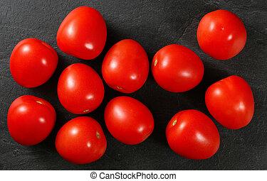 Top down view, dozen of mini tomatoes on black stone desk