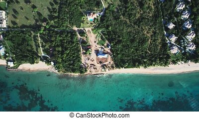 Top-down view of dense forest and rooftops on the seashore in Saint Kitts and Nevis