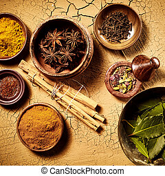 Top down view on pots of assorted whole leaf and ground herbs and spices used as Indian food cooking ingredients over cracked painted brown surface