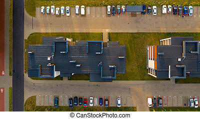 Top down view on multi-family houses and parking with cars.