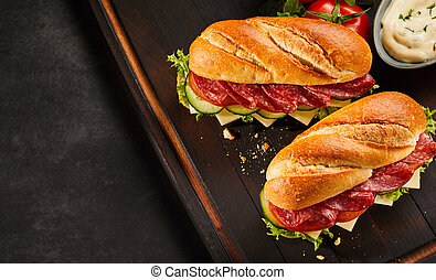 Top down view on pepperoni sandwiches on dark cutting board...