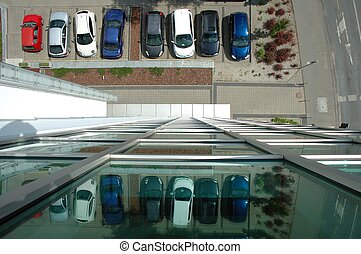 View on car parking from glass facade building