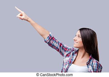 top?, ficar, que, mulher aponta, afastado, cinzento, contra, jovem, enquanto, fundo, sorrindo