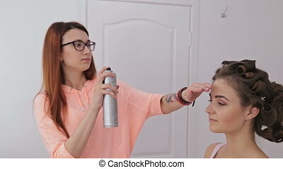 Top knot hair design - hairstylist finishing hairstyle for...