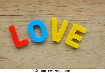 Top lay of the word Love on a wooden background