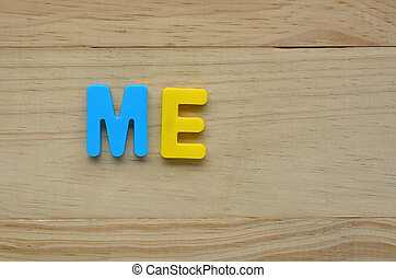 Top lay of the word Me on a wooden background