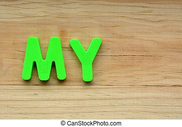 Top lay of the word My on a wooden background