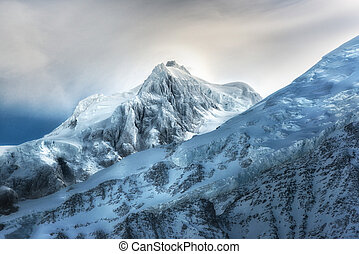 Top of High mountains, covered by snow. Winter mountains on a bright sunny day. Alps mountain landscape with cloudy sky.