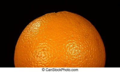 Top of ripe orange isolated on black, rotation
