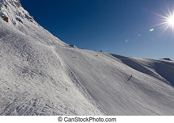 Top of snowy hill in ski resort. Mountain ski slope on a sunny day. Winter mountain landscape